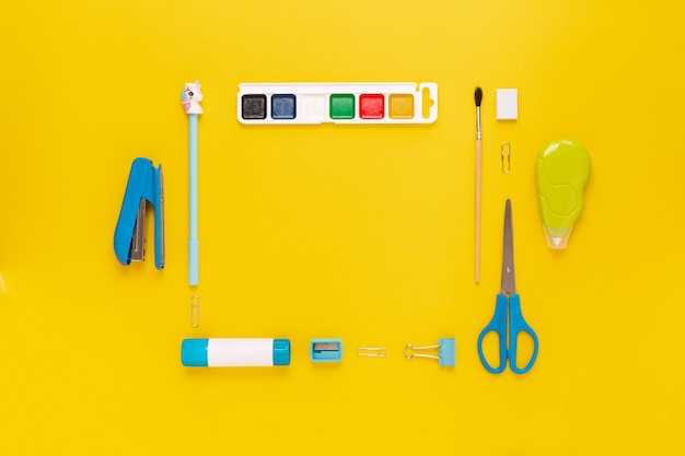 Vista dall'alto del moderno desktop da ufficio bianco, blu, giallo con materiale scolastico e cancelleria sul tavolo intorno allo spazio vuoto per il testo. ritorno al concetto di scuola disteso con mockup