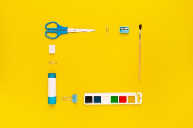 Vista dall'alto del moderno desktop da ufficio bianco, blu, giallo con materiale scolastico e cancelleria sul tavolo intorno allo spazio vuoto per il testo. torna al concetto di scuola disteso con mockup