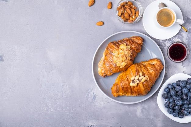 Vista dall'alto della colazione del mattino con caffè, croissant freschi e frutti di bosco. spazio per il testo