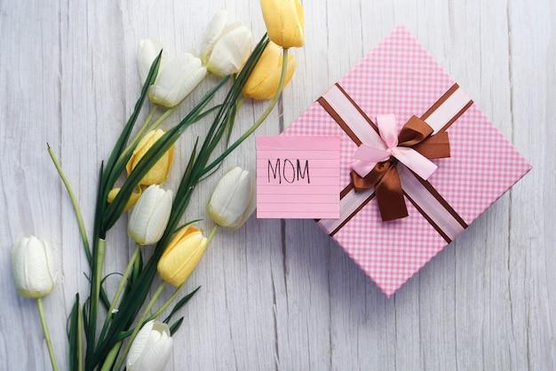 Vista superiore del regalo e del fiore di giorno di madre sulla tavola.