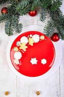 Vista dall'alto mousse torta di natale torta dolce ricoperta di glassa a specchio rosso con decorazioni di capodanno su sfondo bianco, torta europea moderna tema natalizio.