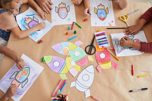 Vista dall'alto di un gruppo multietnico di bambini che disegnano immagini di razzi spaziali con i pastelli mentre si godono lezioni di arte e artigianato nella scuola materna o nel centro di sviluppo
