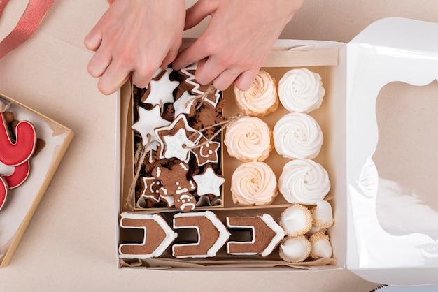Vista dall'alto dolci di capodanno in confezione regalo. gustosi biscotti verniciati glassati e marshmallow e mani femminili