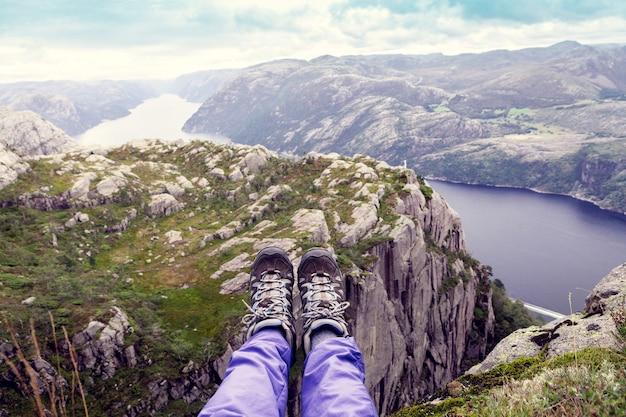 Vista dall'alto del fiordo norvegese con le gambe del turista in primo piano