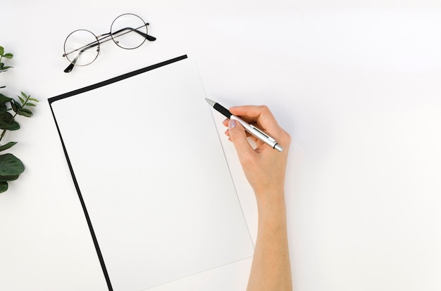 Vista dall'alto del notebook sul desktop con mano e occhiali