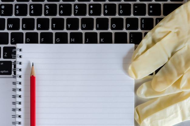 Vista dall'alto di notebook, matita rossa, guanto medico e laptop. studio a distanza del concetto e lavoro da casa durante il periodo di quarantena covid-19