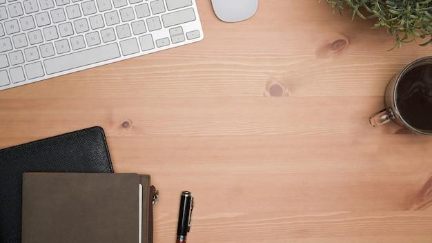 Taccuini, tazza di caffè, tastiera e pianta d'appartamento vista dall'alto sul tavolo di legno.