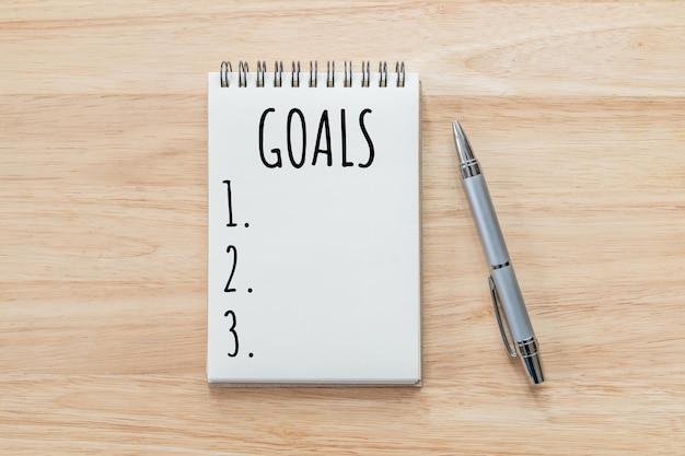 Vista dall'alto del blocco note con l'elenco degli obiettivi sulla tavola di legno, concetto di obiettivi.