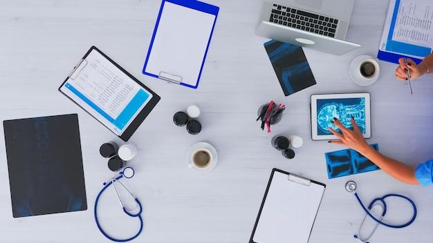 Vista dall'alto dell'infermiera che analizza il cervello umano utilizzando un tablet su flatlay seduto sulla scrivania in clinica con dispositivi a raggi x e digitali