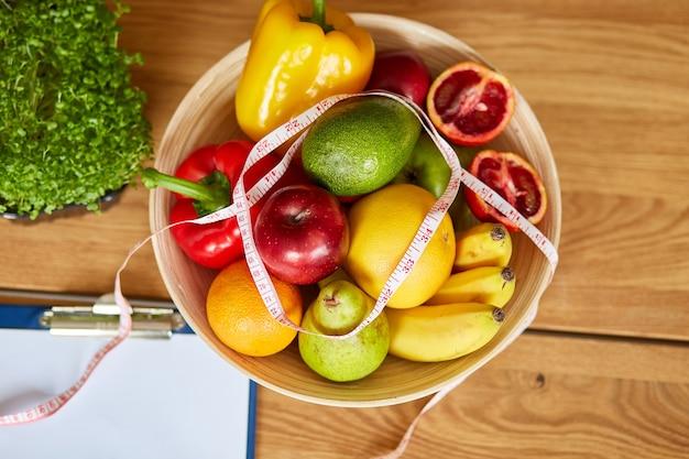 Vista dall'alto del posto di lavoro nutrizionista dietista con spazio vuoto per piano dietetico penna metro a nastro e ciotola con frutta e verdura sane assistenza sanitaria e dieta giusta nutrizione e benessere dimagrante