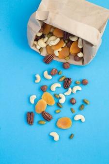 Vista dall'alto di noci e albicocche secche in un sacchetto di carta su sfondo blu