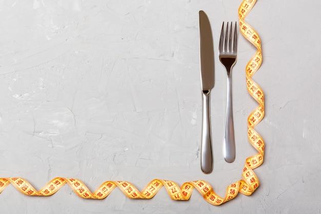 Vista dall'alto del concetto di obesità con forchetta, coltello e nastro di misurazione arricciato sulla superficie del cemento con copyspace