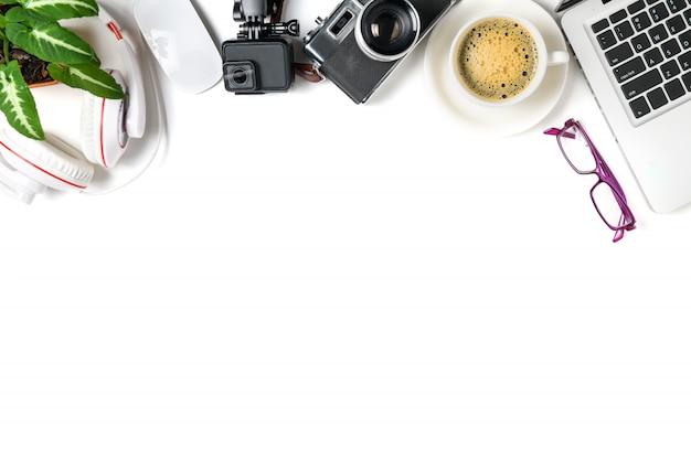 Vista dall'alto del tavolo scrivania da ufficio con tazza di caffè, laptop, action camera e fotocamera vintage isolato su sfondo bianco