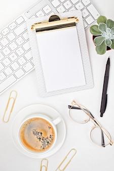Vista dall'alto della scrivania in ufficio. tavolo con tastiera, appunti e forniture per ufficio. area di lavoro piatta dell'ufficio domestico, lavoro a distanza, apprendimento a distanza, videoconferenza, idea di chiamata