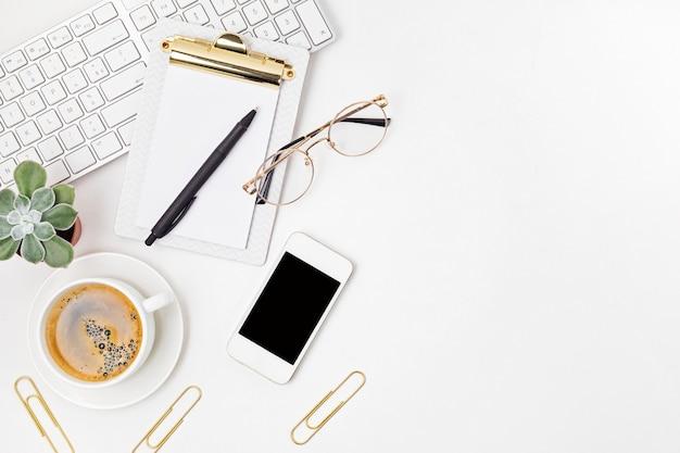 Vista dall'alto della scrivania in ufficio. tavolo con tastiera, smartphone, appunti e forniture per ufficio. area di lavoro piatta dell'ufficio domestico, lavoro a distanza, apprendimento a distanza, videoconferenza, idea di chiamata