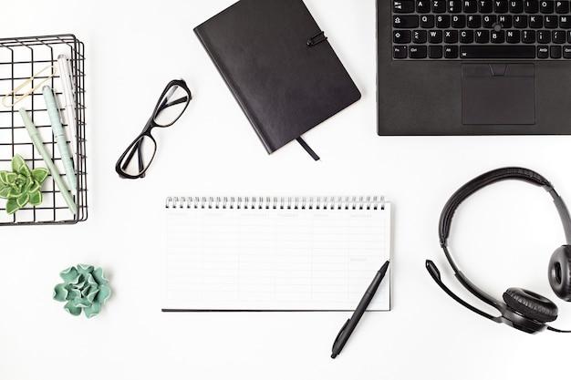 Vista dall'alto della scrivania in ufficio. tavolo con laptop e forniture per ufficio. area di lavoro piatta dell'ufficio domestico, lavoro a distanza, apprendimento a distanza, videoconferenza, concetto di chiamate
