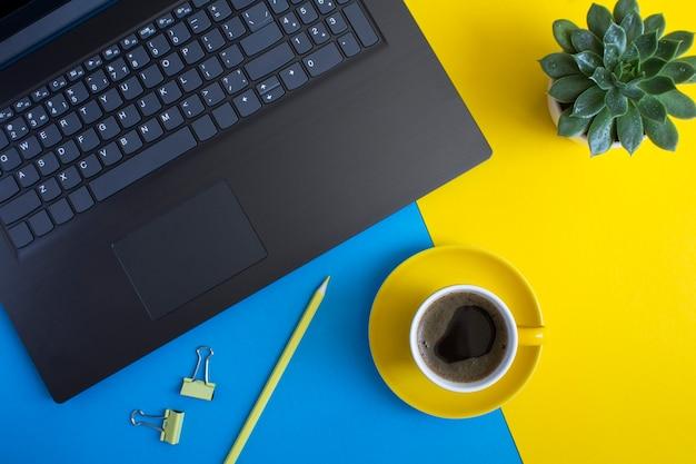 Vista dall'alto della scrivania dell'ufficio con laptop, matita, tazza di caffè e cactus sullo sfondo colorato. disposizione piana della scrivania dell'area di lavoro.