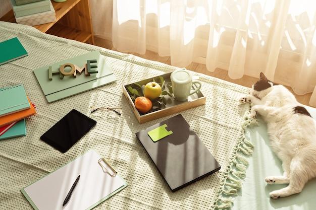 Vista dall'alto di forniture per ufficio nel letto, ambiente di lavoro informale con laptop, blocco note, tazza di tè. lavoro a distanza, ufficio a casa, libero professionista, concetto di auto isolamento