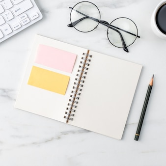 Vista dall'alto del concetto di lavoro scrivania tavolo ufficio con taccuino in bianco