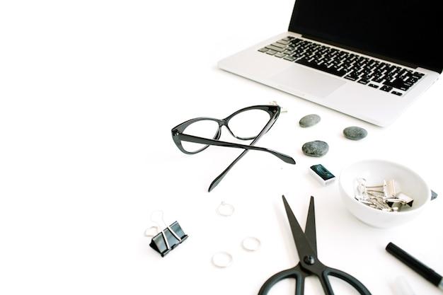 Scrivania tavolo da ufficio vista dall'alto. area di lavoro con laptop, forbici, occhiali, penna su sfondo bianco.