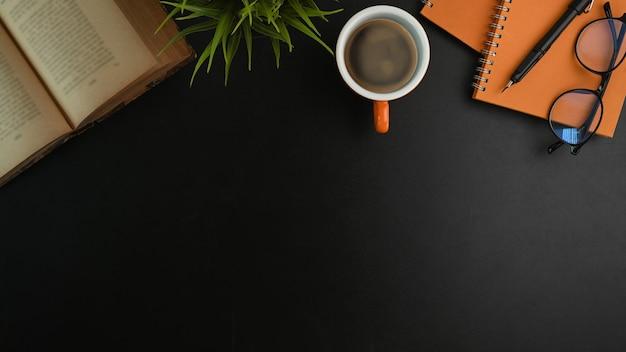 Area di lavoro dell'ufficio vista dall'alto con libro, tazza di caffè, taccuino e pianta sul tavolo nero.