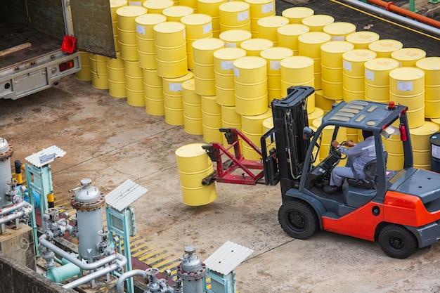 Vista dall'alto barili di petrolio carrello elevatore spostare per il trasporto camion lavoratore maschio aiutare a organizzare.