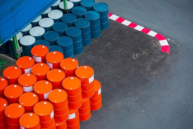 Vista dall'alto barili di petrolio verdi e arancioni o fusti chimici impilati orizzontalmente