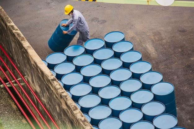 Vista dall'alto barili di petrolio movimento verticale per l'aiuto lavoratore maschio organizzare.