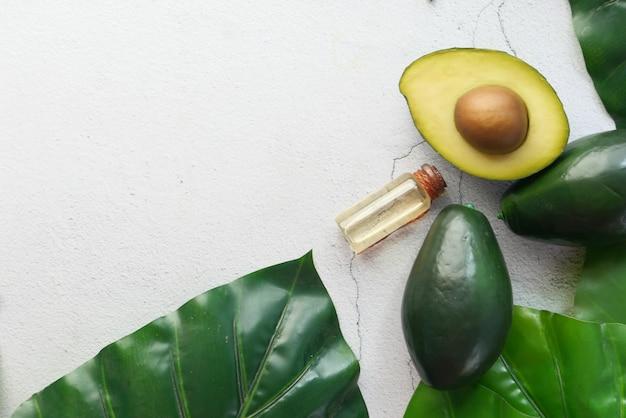 Vista dall'alto di olio e fetta di avocado sulla tavola di legno