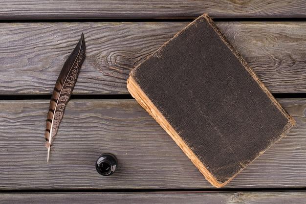 Vecchio libro vista dall'alto con penna e calamaio. vecchio sfondo scrivania.