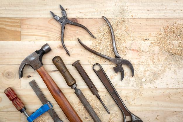 Vista dall'alto del vecchio e arrugginito set di strumenti sul banco da lavoro in legno di pino naturale. concetto di lavoro e fai da te.
