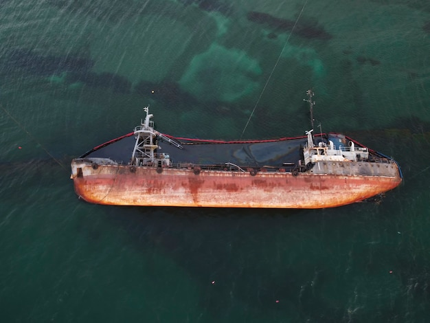 Vista dall'alto di una vecchia petroliera che si è arenata, ha ribaltato e inquinato la costa con fuoriuscite di petrolio. catastrofe ecologica.