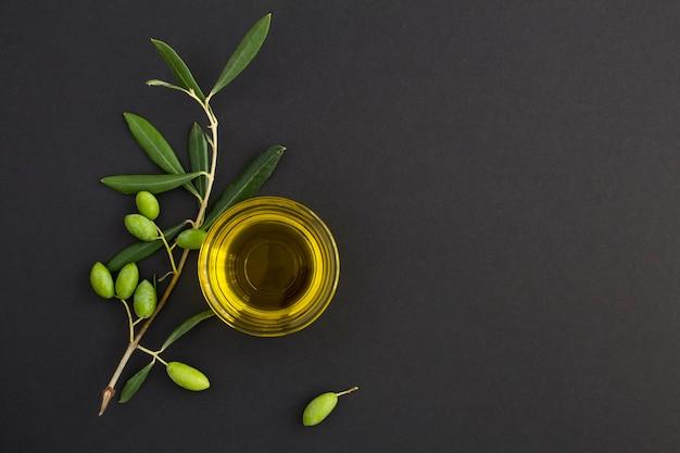 Vista dall'alto dell'olio d'oliva in una ciotola di vetro e ramo con olive verdi su sfondo nero. copia spazio.