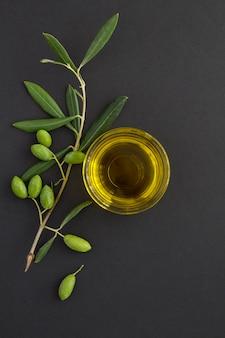 Vista dall'alto dell'olio d'oliva in una ciotola di vetro e ramo con olive verdi su sfondo nero. posizione verticale.