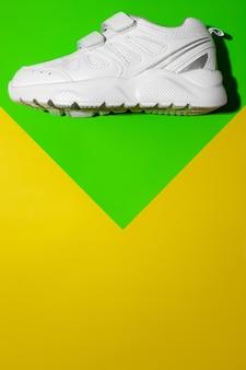 Vista dall'alto una scarpa da corsa bianca sulla parte superiore su uno sfondo geometrico di carta verde e giallo con copia s...