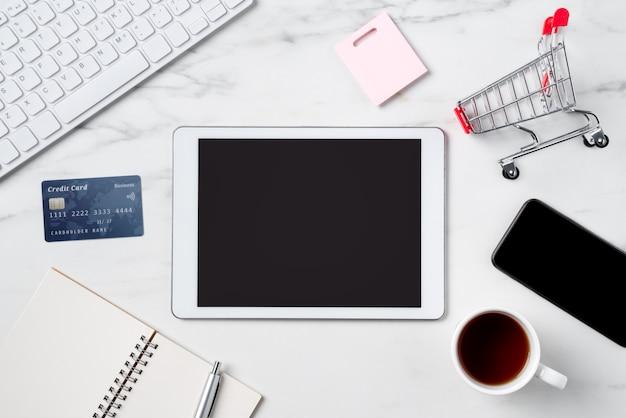 Vista dall'alto del concetto di shopping online con carta di credito ed elettronica isolata sul fondo della tavola bianco marmo ufficio.