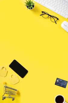 Vista dall'alto del concetto di shopping online con carta di credito, smart phone e computer isolato sul fondo della tavola giallo ufficio.