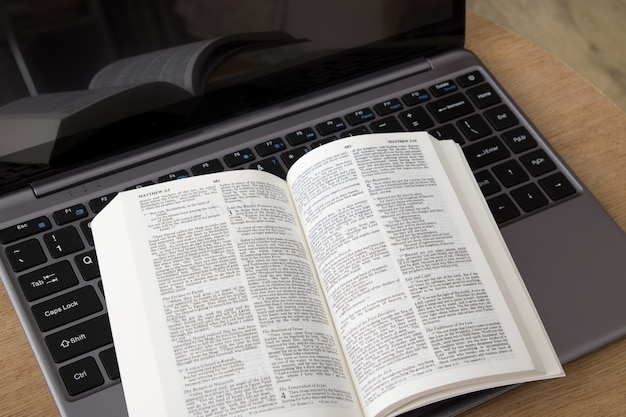 Vista dall'alto di una bibbia aperta su un laptop. studio biblico, adorazione online