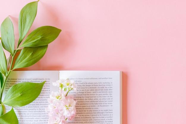 Vista superiore del libro aperto e rosa matthiola incana o mathilda lavanda con ramoscello di ruscus su sfondo rosa pastello con spazio di copia.