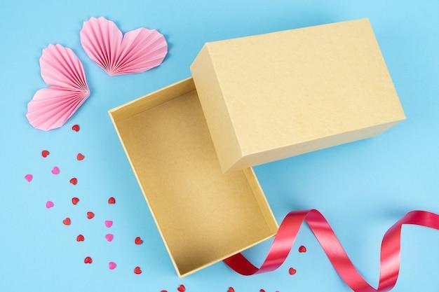 Vista dall'alto della scatola di cartone aperta su sfondo blu con il giorno di san valentino