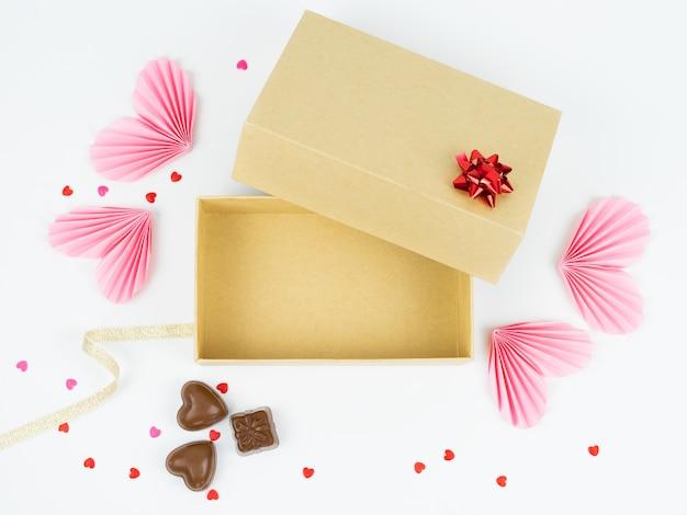 Vista dall'alto della scatola di cartone aperta con decorazioni per san valentino, anniversario, festa della mamma e compleanno. spazio libero per mettere i prodotti. concetto di san valentino.