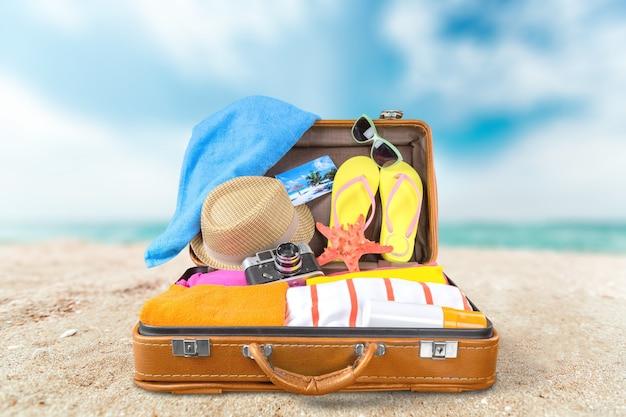 Vista dall'alto di una valigia aperta piena di roba estiva su sfondo blu