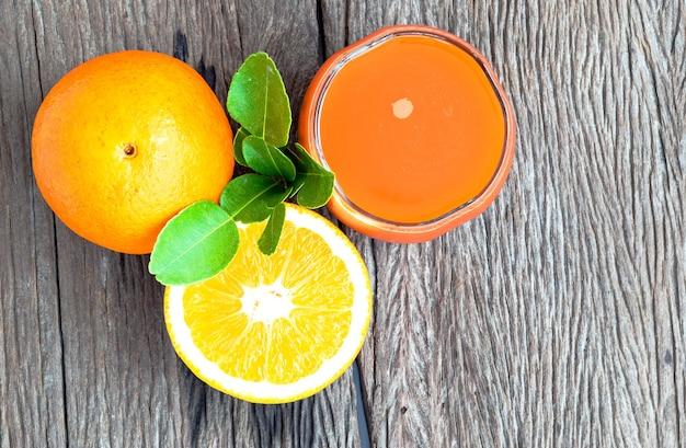 Vista dall'alto del succo d'arancia e delle arance su un pavimento di legno
