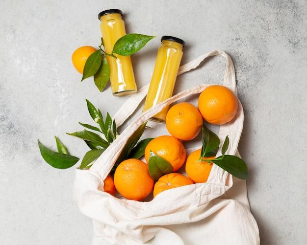 Vista dall'alto arance in borsa di tote con bottiglie di succo