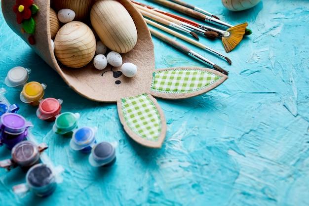 Confezione vista dall'alto di uova con pennello, vernice ed elementi decorativi su sfondo blu. copia spazio, buona pasqua, fai da te, laici piatta. Foto Premium