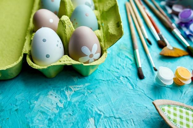 Confezione vista dall'alto di uova con pennello, vernice ed elementi decorativi su sfondo blu. copia spazio, buona pasqua, fai da te, laici piatta.