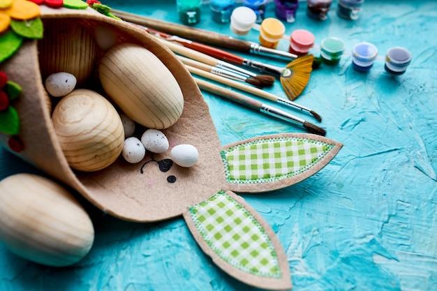 Confezione vista dall'alto di uova con pennello, vernice ed elementi decorativi sulla superficie blu