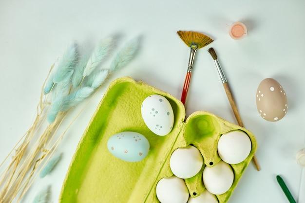 Confezione vista dall'alto di uova con pennello, vernice ed elementi decorativi su sfondo bianco. copia spazio, buona pasqua, fai da te, laici piatta.