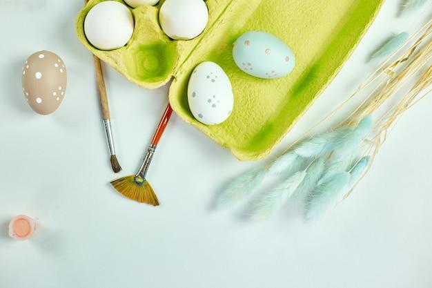 Confezione vista dall'alto di uova con pennello, vernice ed elementi decorativi sulla superficie bianca