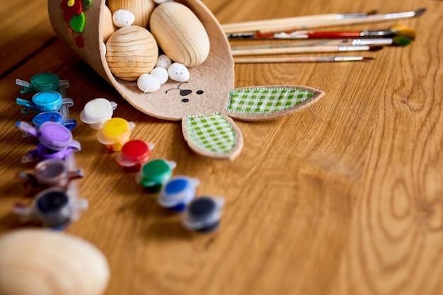 Confezione vista dall'alto di uova con pennello, vernice ed elementi decorativi su fondo in legno. copia spazio, buona pasqua, fai da te, laici piatta.